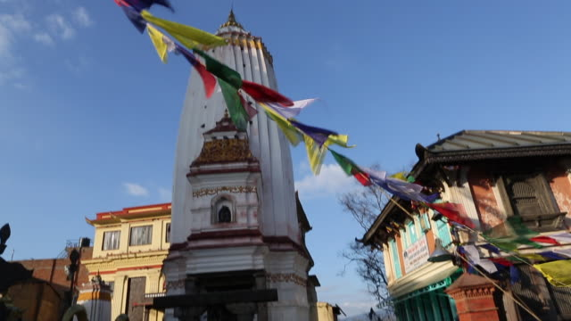 TD of a small temple right next to the Swayambhunath Temple also known as Monkey Temple with prayer flags and allseeing eyes of Buddha in the...