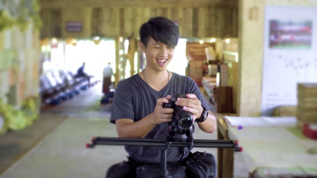 a smile camera man with a mirrorless camera shooting on a cinema with slider at indoor locations. - cinematographer stock videos & royalty-free footage