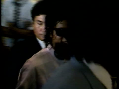 a smiling michael is escorted through swarms of fans and clamoring paparazzi at tokyo, japan airport; crowds of paparazzi in airport taking pictures... - マイケル・ジャクソン点の映像素材/bロール