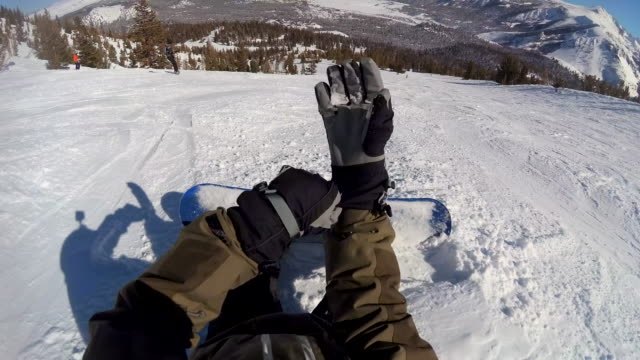 vídeos de stock, filmes e b-roll de pov of a snowboarder buckling into his bindings on his snowboard and putting on gloves. - luvas