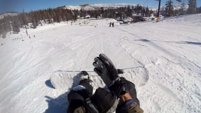 pov of a snowboarder buckling into his bindings on his snowboard. - mammoth lakes video stock e b–roll