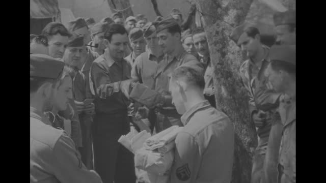 a soldier holding large bundles of parcels calls out for distribution; several views of good-natured soldiers and women reading their mail - reading mail stock videos & royalty-free footage