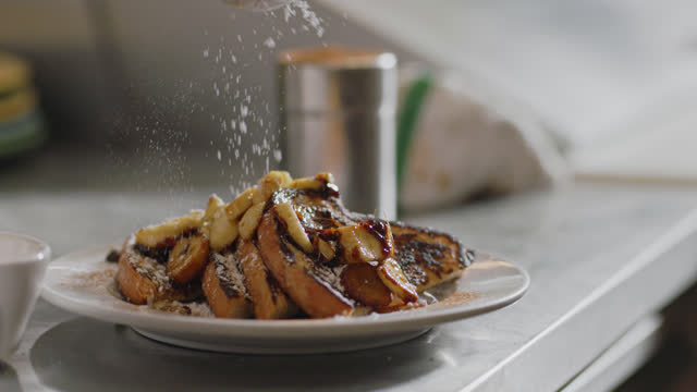 slo mo. cu of a steaming hot plate of delicious slices of banana french toast covered in powdered sugar in an authentic diner - nut food stock videos & royalty-free footage