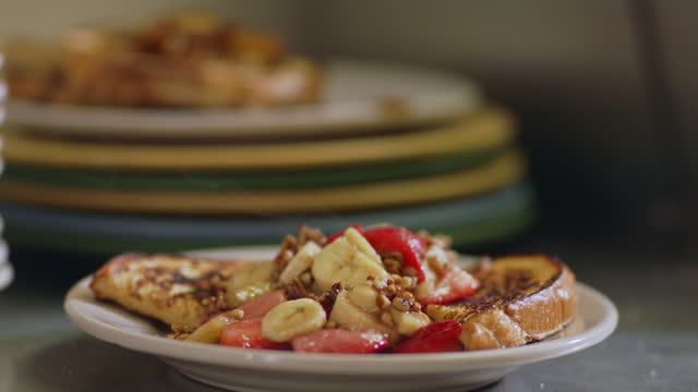 slo mo. cu of a steaming hot plate of delicious slices of banana pecan french toast covered in bright red strawberries in an authentic diner - commercial kitchen stock videos & royalty-free footage