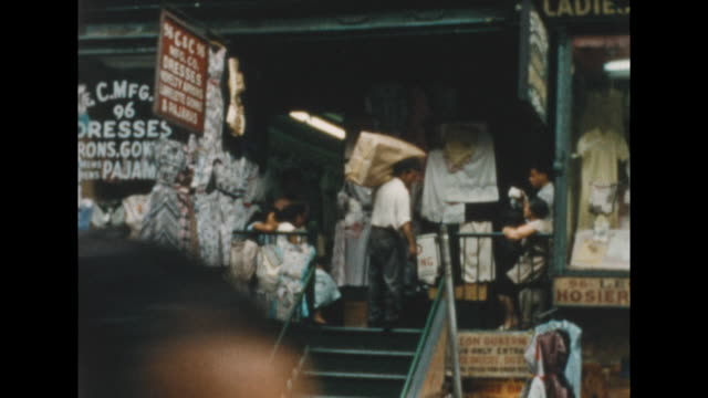 ws of a store in new york's lower east side advertising dresses aprons gowns and pajamas man carries a large package into the store three african... - pyjamas stock videos & royalty-free footage