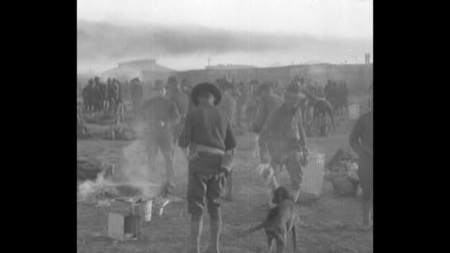 a supply train is unloaded by american soldiers in a dusty area with a two mule team at the lower left / pan right of a large camp with american... - 1910 stock videos & royalty-free footage