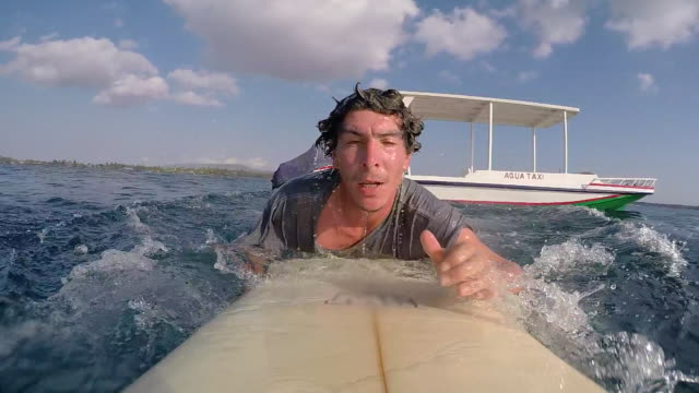pov of a surfer diving in off a aqua water taxi on his surfboard. - slow motion - water taxi stock videos & royalty-free footage