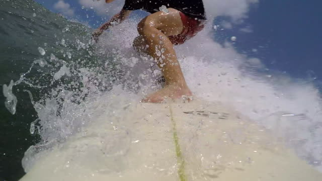 POV of a surfer surfing waves on his surfboard.