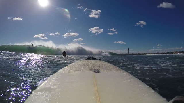 POV of a surfer surfing waves on his surfboard wearing a full wetsuit. - Slow Motion
