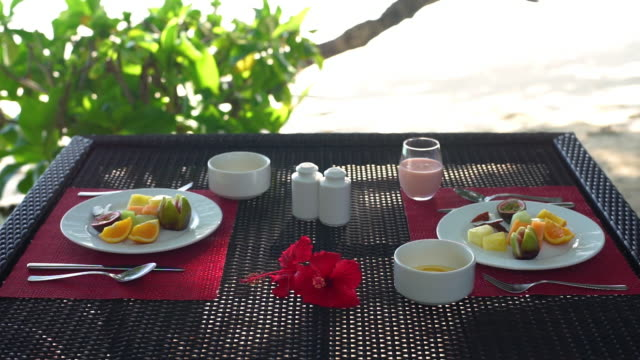 cu of a table set with two breakfasts and people drinking smoothies - tourist resort stock videos & royalty-free footage