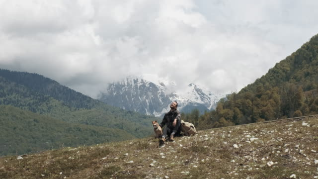vidéos et rushes de a tall man with a backpack walks with his dog in the mountains - eastern european culture