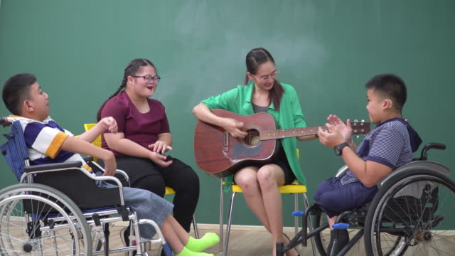 a teenage boy with a disability in wheelchair and girl with down syndrome sitting and having music class and therapy with an asian teacher in the school. beautiful woman playing guitar and sharing relaxation moments and happiness with students. - music therapy stock videos & royalty-free footage