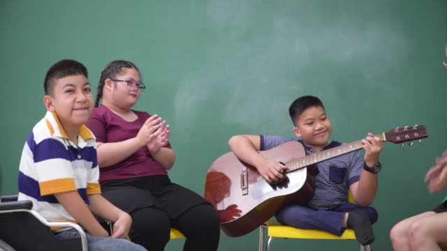 a teenage boy with a disability in wheelchair and girl with down syndrome sitting and having music class and therapy with an asian teacher in the school. boy having the ability to playing guitar and sharing relaxation moments and happiness with friends. - music therapy stock videos & royalty-free footage