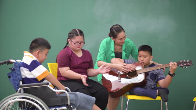 a teenage boy with a disability in wheelchair and girl with down syndrome sitting and having music class and therapy in the school. asian teacher teaching boy how to playing guitar and sharing relaxation moments and happiness with his friends. - music therapy stock videos & royalty-free footage
