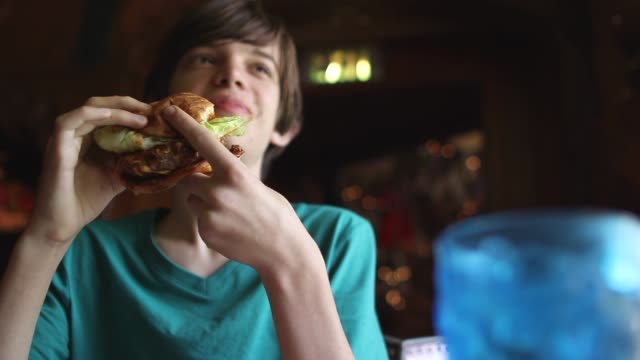 vídeos y material grabado en eventos de stock de a teenager is eating a hamburger - fast food