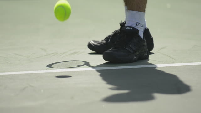 CU ECU of a tennis player's feet and shadow of a racket and the tennis ball bouncing.