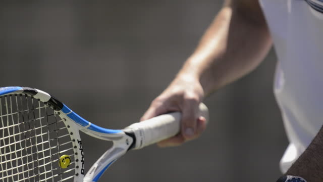 cu ecu a tennis racquet and player bouncing the ball and getting ready to serve. - racquet stock videos & royalty-free footage