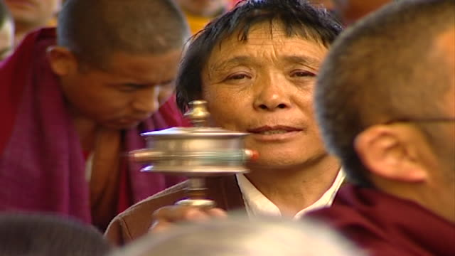 of a tibetan worshipper spinning a prayer wheel listening to hh dalai lama giving a sermon at tsuglagkhang temple. the 14th dalai lama lives in exile... - worshipper stock videos & royalty-free footage