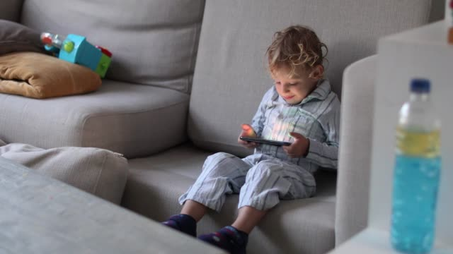 a toddler stares blankly at a mobile phone. - zombie stock videos & royalty-free footage