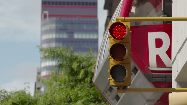 cu of a traffic light.  the roosevelt island tram takes off directly behind the light. - verkehrs leuchtsignal stock-videos und b-roll-filmmaterial