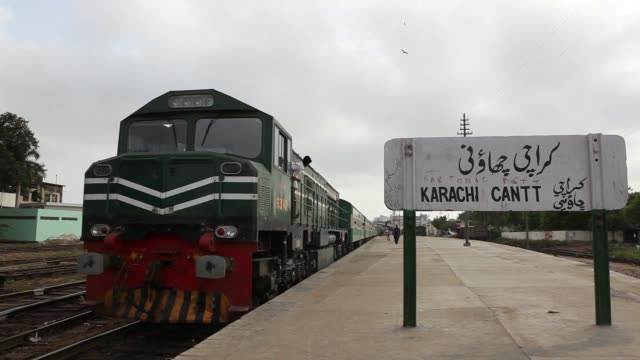 ws a train moves along on a railroad track ms front of train approaching on a railroad track ws sign for karachi cantonment station right as train... - rail transportation stock videos & royalty-free footage