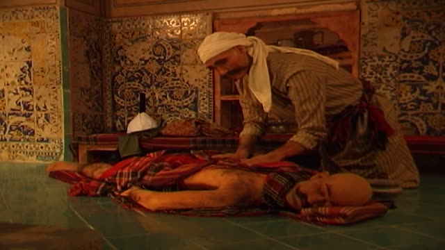 of a wax figurine of a masseur in traditional clothes wearing a turban giving a client a massage in a safavid era bath house. - masseur stock videos & royalty-free footage