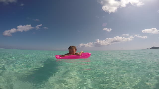 a woman and her child lying on an inflatable mattress in the sea - standing water stock videos & royalty-free footage