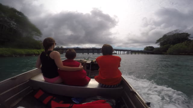 stockvideo's en b-roll-footage met a woman and two children on a small motorboat on the sea with a threatening sky - huahine