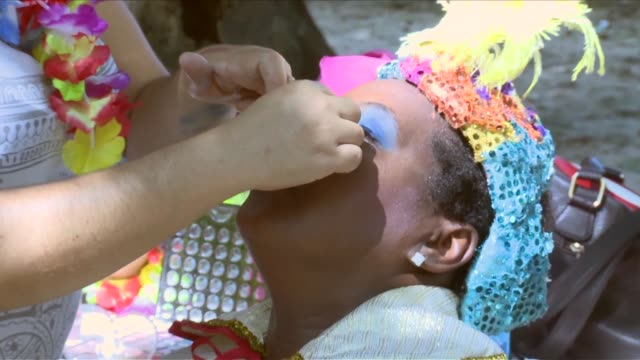 "CU a woman getting Carnival make up put on Patients of the ""Insituto Municipal Nise de Silveria"" mental hospital prepare for and celebrate the 2014..."
