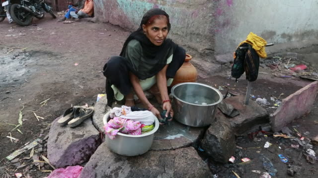 of a woman in a black sari is doing laundry on a flagged floor in a small village on march 28, 2013 in bijapur, india. a silver bucket with water can... - slum stock videos & royalty-free footage