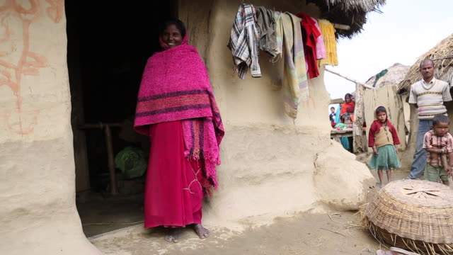 ws pan of a woman in a pink sari that is standing in front of a mud hut while laundry is drying up next to her in a rural village near birgunj a... - strohdach stock-videos und b-roll-filmmaterial