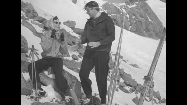 VS a woman in sunglasses and her companion with skis arrive at rocky outcropping in the snow / she stands at table and the man brings her a pair of...