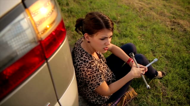 a woman is waiting for help on the road,flat tire