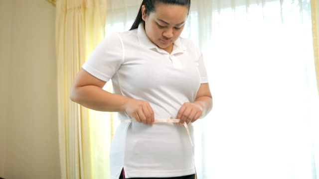 a woman measuring her stomach - measuring stock videos & royalty-free footage