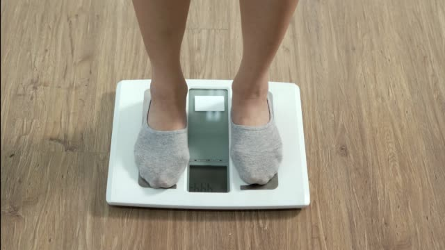 a woman walks in her house and she walks on the scale to check her body weight on the manual weight scale - dieting stock videos & royalty-free footage