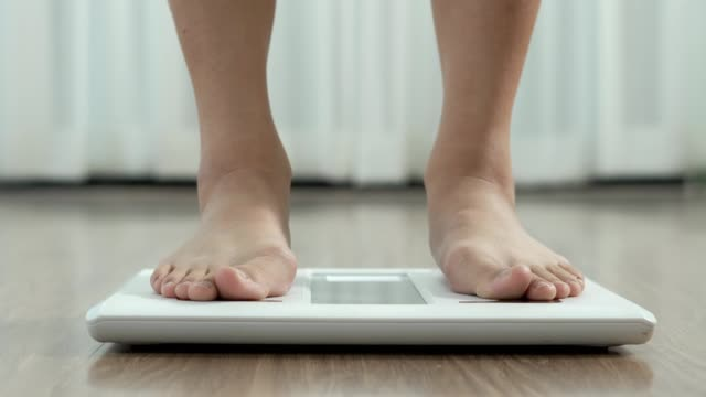 a woman walks in her house and she walks on the scale to check her body weight on the manual weight scale - overweight patient stock videos & royalty-free footage