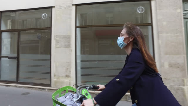 a woman with a protective mask, on a bicycle in the streets of paris. 4 may, 2020 in paris, france. - city life stock videos & royalty-free footage