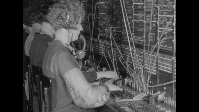 vs a woman with short hair speaks into a microphone while moving cords around a switchboard other women do the same nearby / note exact year not... - repetition stock videos and b-roll footage