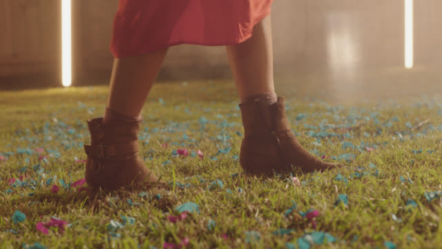 slo mo. cu of a woman's boots dancing on grass covered with confetti - stivale video stock e b–roll