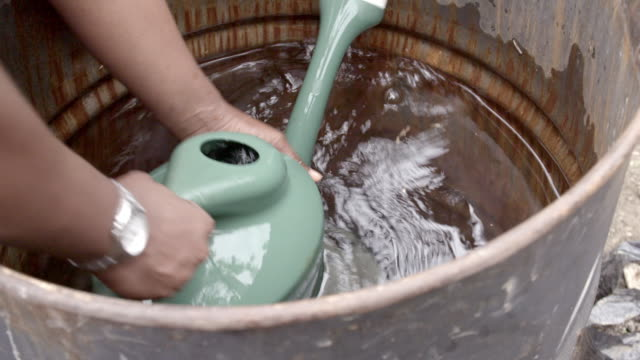 CU of a woman's hands filling up a watering can
