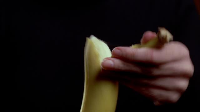 CLOSE UP a woman's hands peel a banana