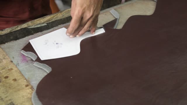 a worker cuts designs out of leather hides in the design section of a workshop in agra, uttar pradesh, india, on wednesday, june 21, 2017 - indian subcontinent ethnicity stock videos & royalty-free footage