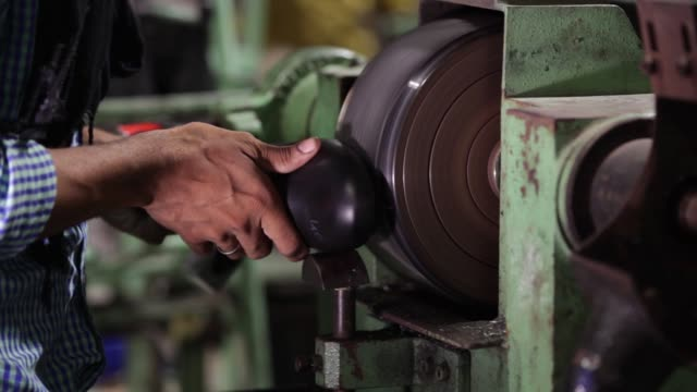 CU a worker uses a grinding machine on the assembly line at a Virola Shoes Pvt manufacturing facility in Agra Uttar Pradesh India on Friday June 23...