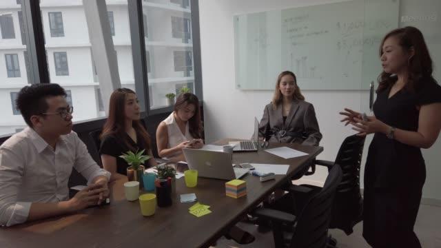 vidéos et rushes de un jeune dirigeant chinois asiatique dirige une réunion dans la salle de réunion en fonction avec ses collègues - table de salle de réunion