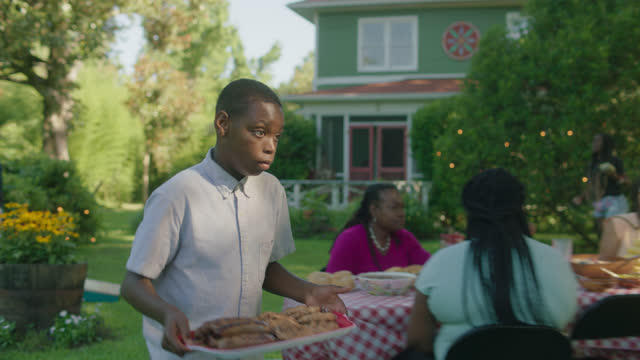 ms of a young boy carrying food out to the grill - african american ethnicity stock videos & royalty-free footage
