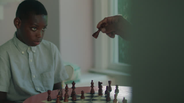MS of a young boy learning how to play chess
