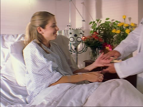 a young caucasian female patient sits in her hospital bed as an elderly doctor arrives to talk with her - auf dem rücken liegen stock-videos und b-roll-filmmaterial