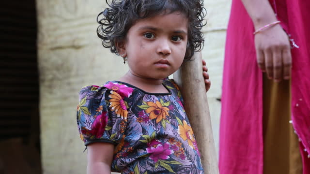 CU of a young girl in a floral pattern dress standing next to a post in a small village on March 28 2013 in Bijapur India Around 50000 people are...