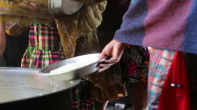 CU of a young girl who is serving food with a ladle out of a big cooking pot to school children who are standing in line with silver plates in their...