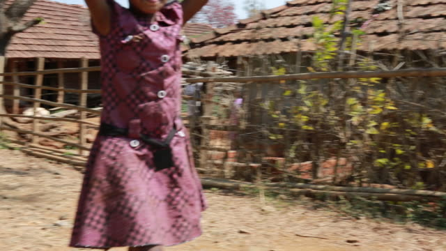 ws pan of a young girl who is walking down a bumpy farm track while she is carrying several bowls on the head in a small village in a rural area... - bumpy stock videos & royalty-free footage